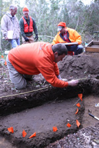 Archaeologists mapping a feature which is outlined by the orange flags. Photograph by Lance Cpl. Nikki S. Phongsisattanak