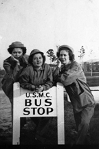 "Women Marines around sign, circa 1944. Three Women Marines pose around a sign at Camp Lejeune that reads ""U.S.M.C. Bus Stop."" The women wear olive-drab work overalls, men's work jackets, and ""daisy mae"" fatigue hats.  Nina Johnson Wiglesworth Papers Collection (WV0132.6.008), Betty H. Carter Women Veterans Historical Project, University of North Carolina at Greensboro, NC."
